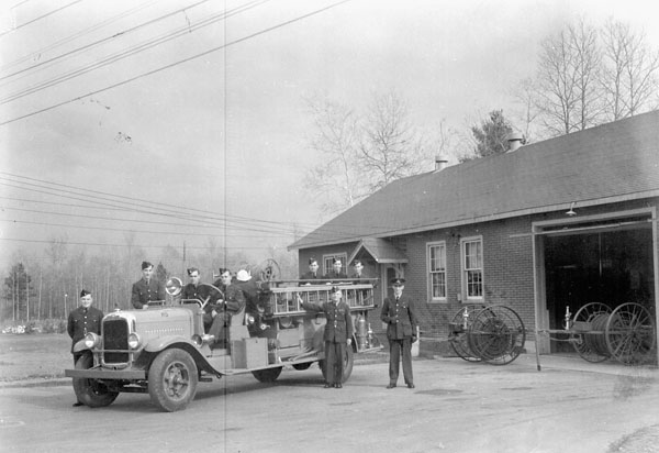 Personnel with a firetruck, No.1 Service Flying Training School (Royal Canadian Airforce Schools and Training Units), Royal Canadian Air Force (R.C.A.F.), Camp Borden, Ontario, Canada, October 1944.