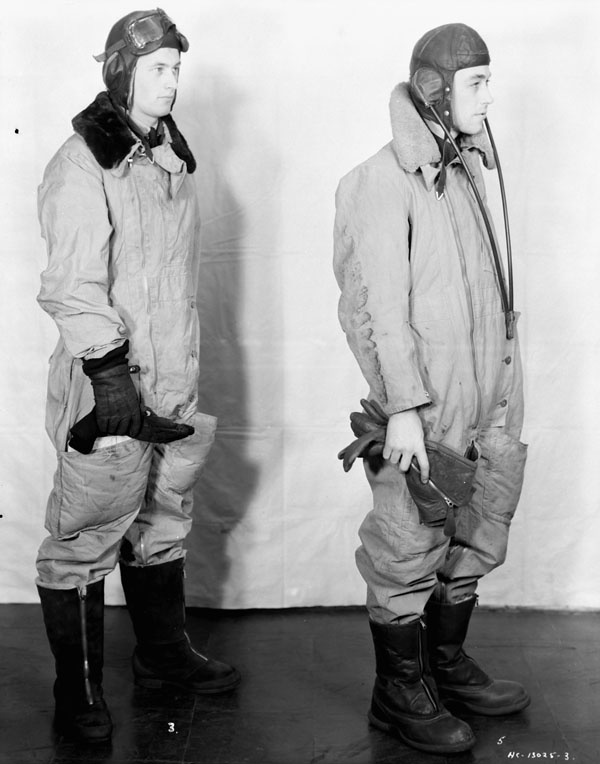 Unidentified airmen modelling two types of flying suits, Test and Development Establishment, R.C.A.F. Station Rockcliffe, Ontario, Canada, 12 January 1943.