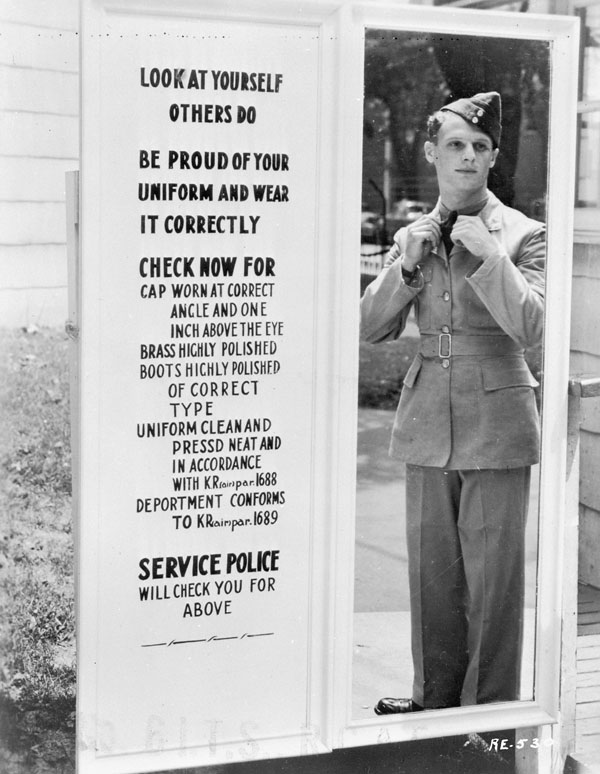 An unidentified airman checking his uniform in a mirror before passing through the exit gate at RCAF Station.