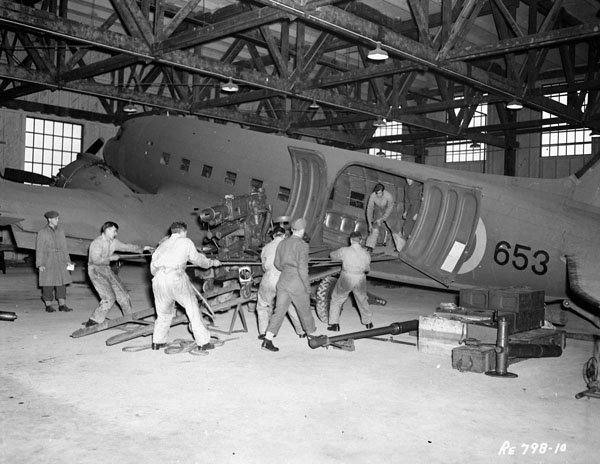 Air transportability trials: personnel loading a field gun into Douglas Dakota III aircraft 653 of No.12(Comm) Squadron, Royal Canadian Air Force, Rockcliffe, Ontario, Canada, 28 October 1943.