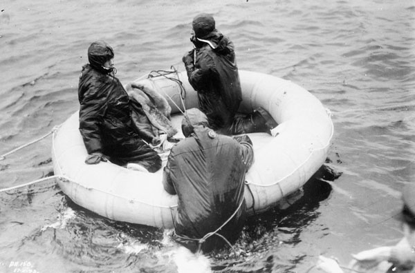 Personnel wearing aircrew survival suits in a dinghy in the Ottawa River, Test and Development Establishment, R.C.A.F. Station Rockcliffe, Ontario, Canada, 27 December 1943.