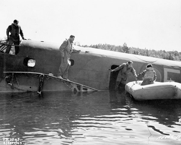 Personnel demonstrating the use of a dinghy during the simulated crash landing of a Lockheed Ventura aircraft in the Ottawa River, Test and Development Establishment, R.C.A.F. Station Rockcliffe, Ontario, Canada, 29 November 1943.