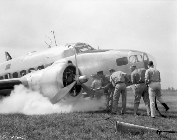 Personnel extinguishing a fire under the starboard wing of a Lockheed Lodestar aircraft which ground-looped while landing at R.C.A.F. Station Rockcliffe, Ontario, Canada, 7 September 1944.