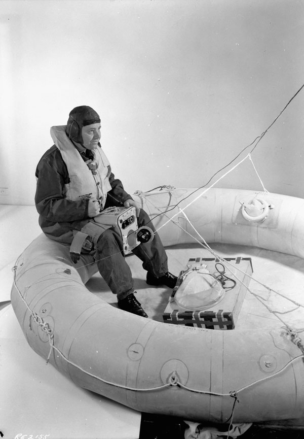 Unidentified airman sitting in an H-type dinghy displaying a Gibson Girl emergency transmitter, Test and Development Establishment, R.C.A.F. Station Rockcliffe, Ontario, Canada, 25 November 1944.