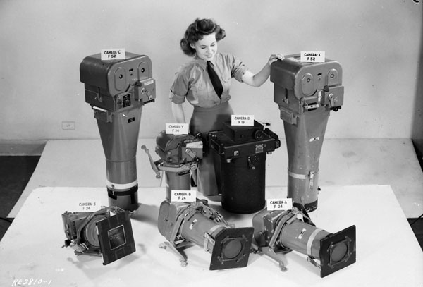 Unidentified airwoman displaying types of aerial cameras used by the Royal Canadian Air Force in Operation Eclipse to photograph a solar eclipse. R.C.A.F. Station Rockcliffe, Ontario, Canada, 19 July 1945.