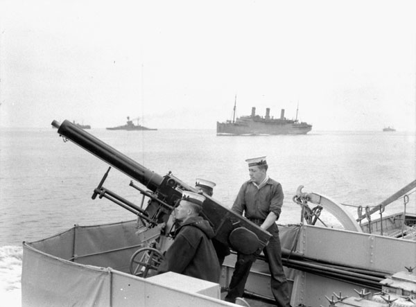 Unidentified ratings manning a two-pounder anti-aircraft gun aboard H.M.C.S. ASSINIBOINE, which is escorting a troop convoy en route from Halifax to Britain, 10 July 1940.