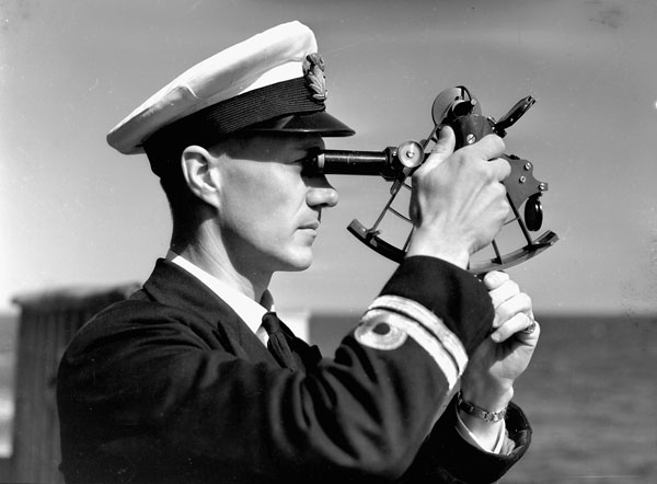 Lieutenant John H. Stubbs, who is using a sextant, on the bridge of the destroyer H.M.C.S. ASSINIBOINE off Halifax, Nova Scotia, Canada, September 1940.