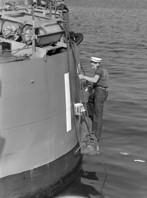 "Unidentified rating painting the pendant number ""H 00"" on the stern of H.M.C.S. RESTIGOUCHE during her refit at Halifax, Nova Scotia, Canada, October 1940"