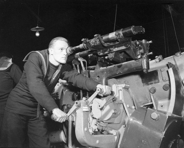 Unidentified rating operating the training mechanism of a 4.7-inch gun, Royal Canadian Navy Gunnery School, Halifax, Nova Scotia, Canada, 1940.