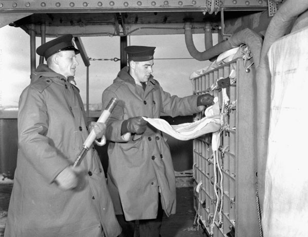 Unidentified signals personnel at the flag locker of the armed merchant cruiser H.M.C.S. PRINCE DAVID, Halifax, Nova Scotia, Canada, January 1941.