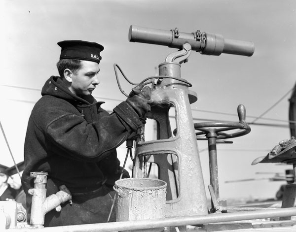 Unidentified rating painting a fitting aboard an unidentified Town-class destroyer of the Royal Canadian Navy, Halifax, Nova Scotia, Canada, March 1941.