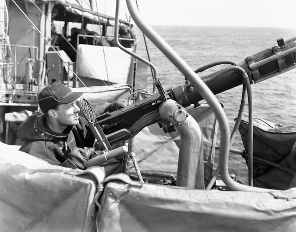 Unidentified rating manning a .50-calibre machine gun aboard H.M.C.S. ST CROIX at sea, March 1941.