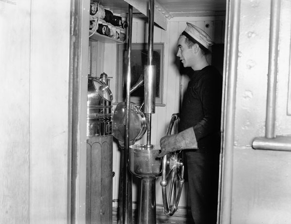Unidentified rating in the wheelhouse of the fuel oil carrier H.M.C.S. MOONBEAM, Halifax, Nova Scotia, Canada, April 1941.