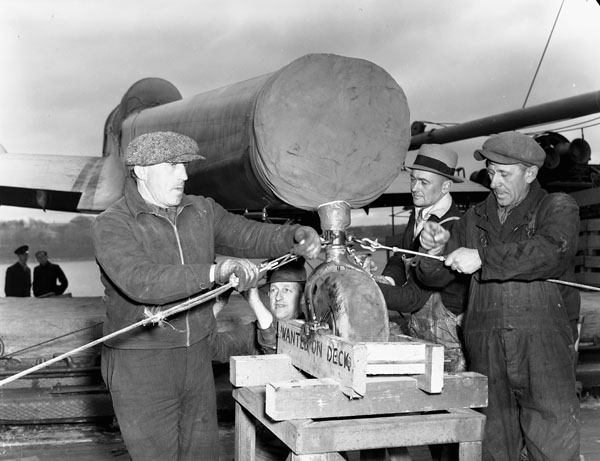 Workers securing a Handley Page Hampden aircraft to the deck of a merchant ship en route to England. Halifax, Nova Scotia, Canada, April 1941.