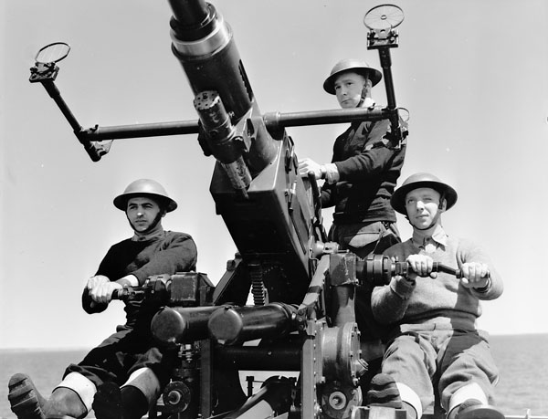 Unidentified DEMS (Defensively Equipped Merchant Ships) gunners manning a Bofors 40mm. anti-aircraft gun aboard an unidentified merchant ship  at sea, 5 May 1941.