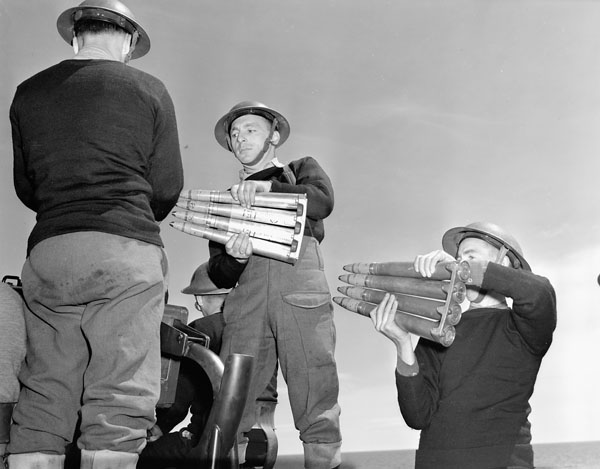Unidentified DEMS (Defensively Equipped Merchant Ships) gunners passing ammunition for a Bofors 40mm. anti-aircraft gun aboard an unidentified merchant ship at sea, 5 May 1941.