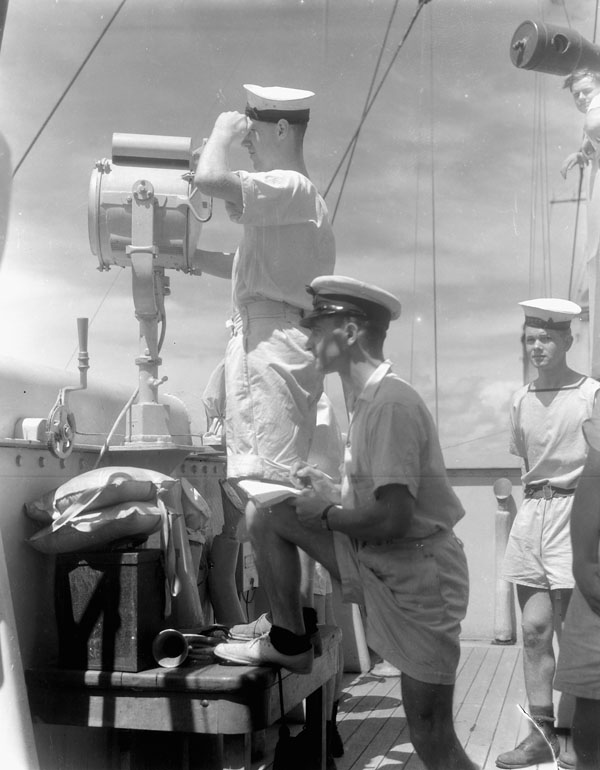 Signallers aboard H.M.C.S. PRINCE HENRY reading a signal from H.M.S. CIRCASSIA off Bermuda, October 1941.