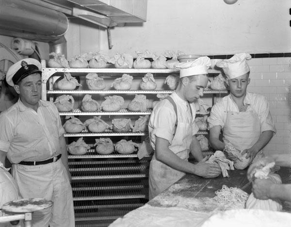 Petty Officer Cook Bert Grant (left) and his assistants preparing Christmas puddings, H.M.C.S. STADACONA, Halifax, Nova Scotia, Canada, December 1941.