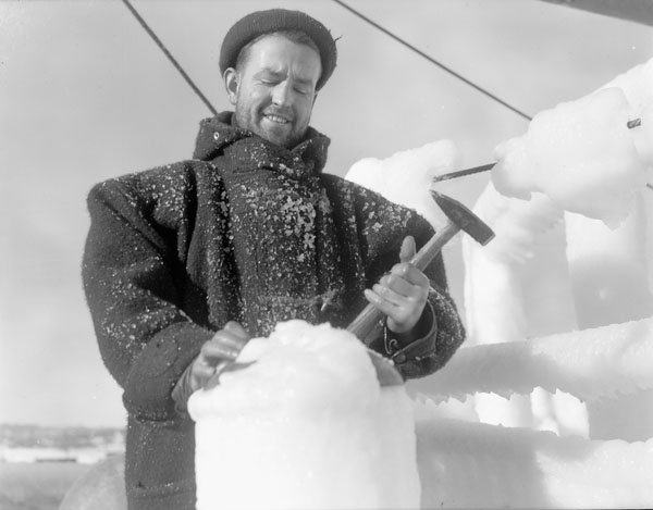 Seaman Gunner R. E. Walsh chopping ice from the superstructure of the corvette HMCS Lunenburg.