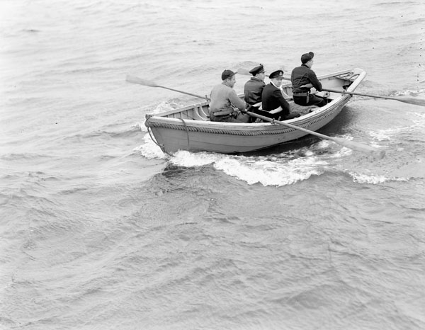 Officers of the R.C.N. Naval Control Service returning to their examination vessel after inspecting a merchant ship, Halifax, Nova Scotia, Canada, May 1942.