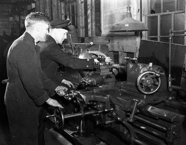 Electrical Artificers operating a lathe in the Electrical Artificers' Workshop, H.M.C. Dockyard, Halifax, Nova Scotia, Canada, 18 November 1942.