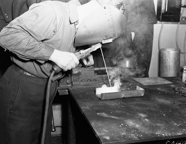 An Electrical Artificer doing arc-welding in the Electrical Artificers' Workshop, H.M.C. Dockyard, Halifax, Nova Scotia, Canada, 18 November 1942.