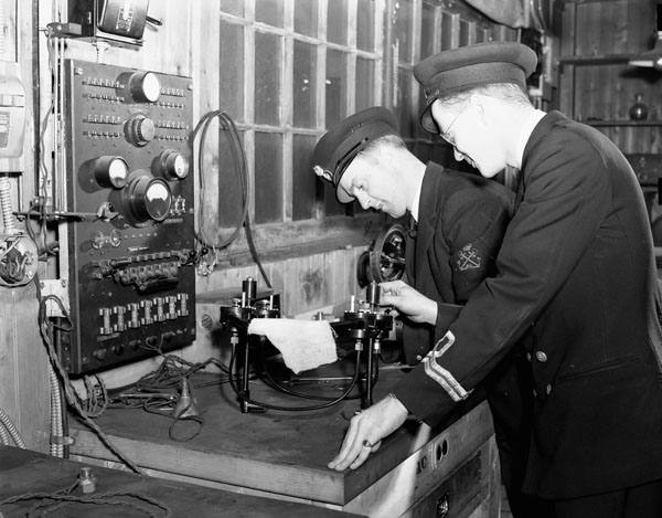 An unidentified Lieutenant watching an Electrical Artificer working on electrical equipment in the Electrical Artificers' Workshop, H.M.C. Dockyard, Halifax, Nova Scotia, Canada, 18 November 1942.