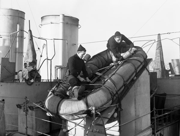 Unidentified personnel, who are wearing woolen clothing supplied by The Canadian Red Cross Society, making a Carley raft ready for sea aboard an unidentified ship of the Royal Canadian Navy, Halifax, Nova Scotia, Canada, 5 February 1943.
