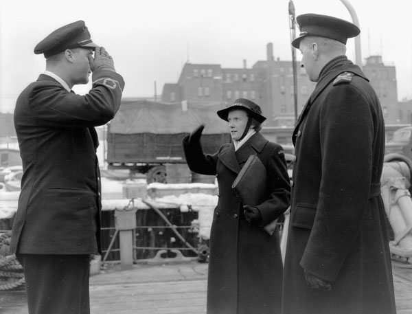 Wren Gibbs (centre) of the Women's Royal Canadian Naval Service (W.R.C.N.S.) delivering a message to the minesweeper H.M.C.S. ESQUIMALT, Halifax, Nova Scotia, Canada, 2 February 1943.