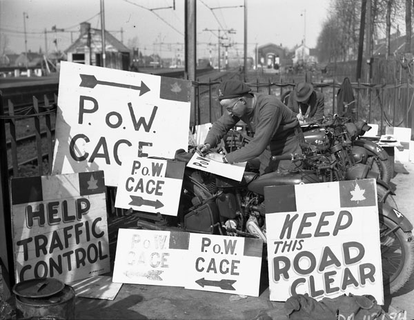 Lance-Corporal H.G. Roseborough of No. 8 Provost Company, Canadian Provost Corps, painting signs.