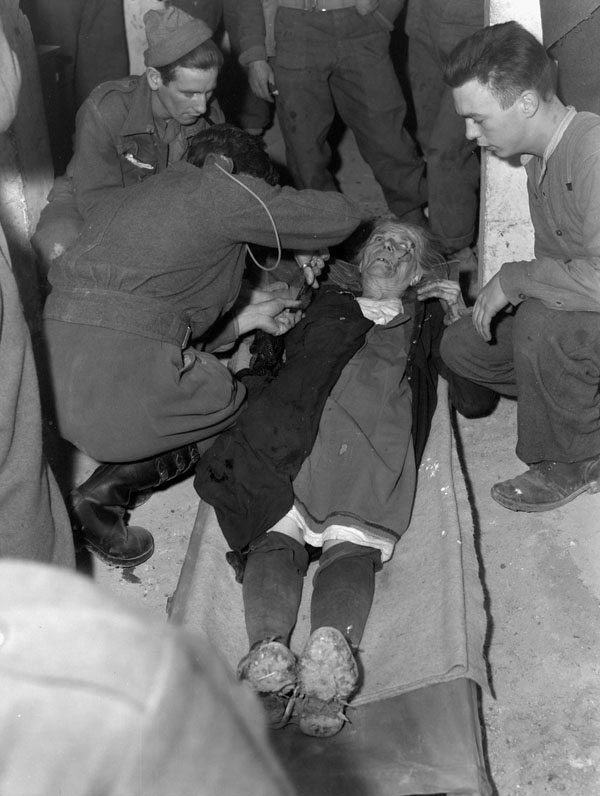 Major P.K. Tisdale treating a wounded Italian woman at the Advanced Dressing Station of No.4 Canadian Field Ambulance, Royal Canadian Army Medical Corps (R.C.A.M.C.)., San Vito di Ortona, Italy, 15 January 1944.
