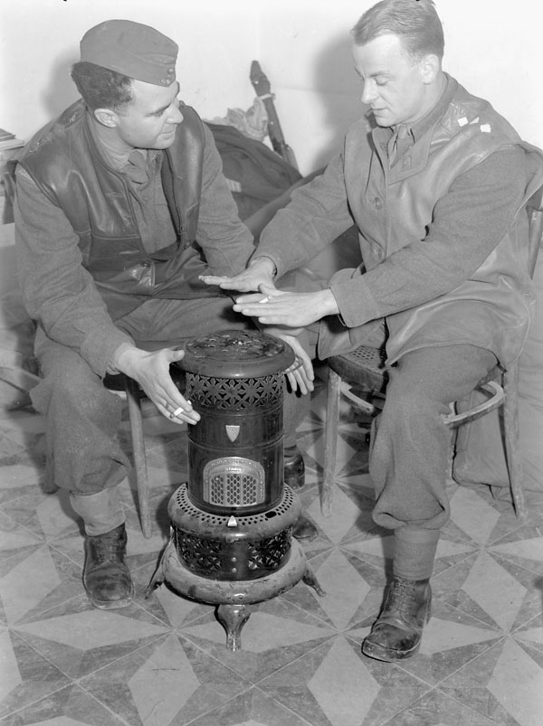 Canadian officers warming themselves at a stove, San Vito Chietino, Italy, 13 January 1944.
