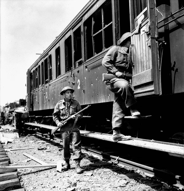 Infantrymen of the Stormont, Dundas and Glengarry Highlanders searching railway cars, Vaucelles, France, 18 July 1944.
