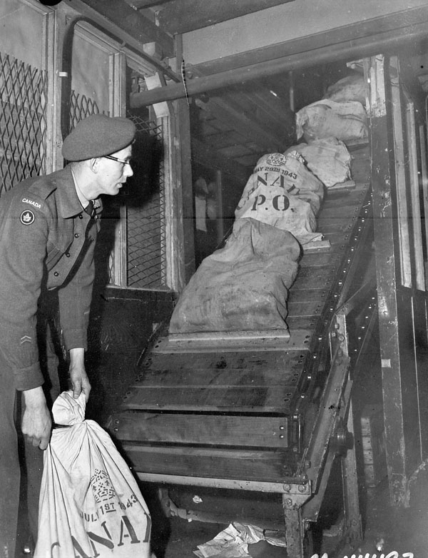 Private E.S. Tooke loading bags of mail, No.1 Canadian Overseas Postal Depot, Canadian Postal Corps (C.P.C.), London, England, 30 May 1945.