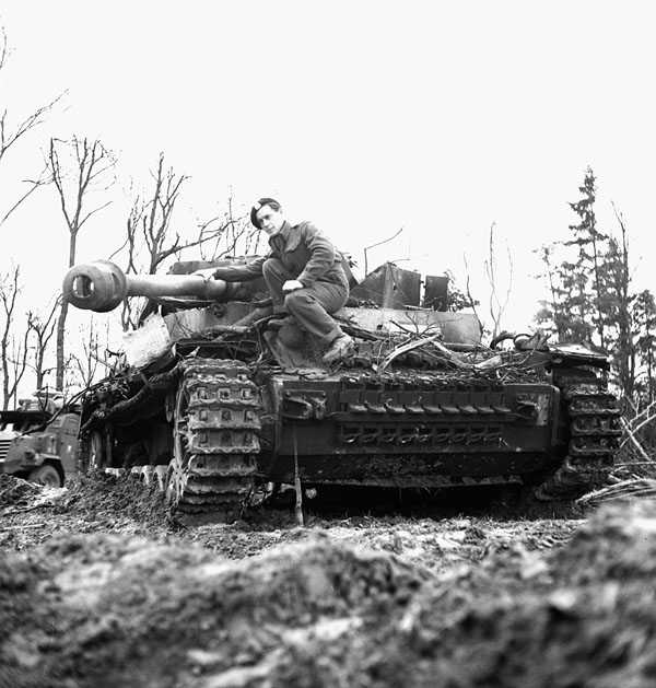 Trooper  M.E. Lucy of The South Alberta Regiment examining a German 75mm. self-propelled gun near Xanten, Germany, 7 March 1945.