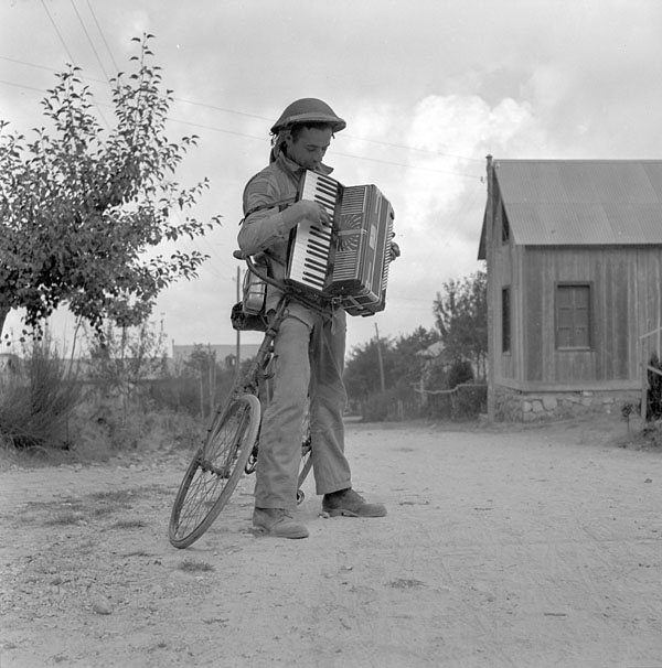 Private A.R. Quinn, Princess Patricia's Canadian Light Infantry (P.P.C.L.I.), with captured accordion, Gambarie, Italy, September 1943.