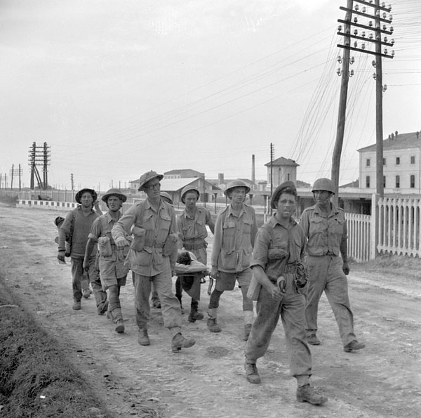 Sgt. Ronnie Leather, Toronto, ON, of the Three Rivers Regiment, on a stretcher after being hit in the tank he commanded, near Termoli, Italy, 6 October 1943.