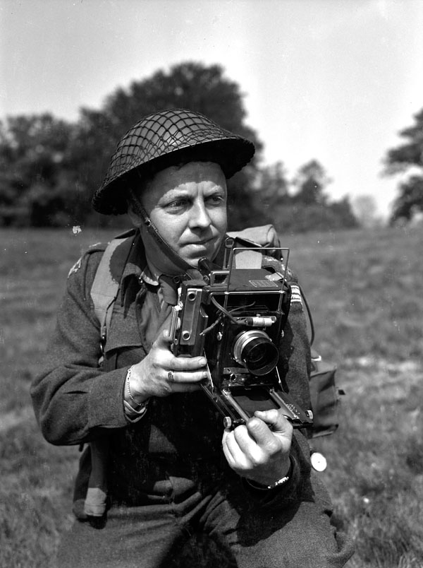 Lieutenant Frank L. Dubervill of the Canadian Army Film and Photo Unit, holding an Anniversary Speed Graphic camera, England, 11 May 1944.