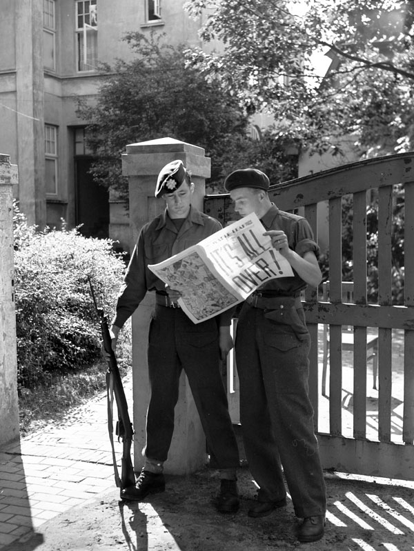 Personnel of the Canadian Army Occupation Force reading the news of the surrender of Japan, Westerstede, Germany, 16 August 1945.