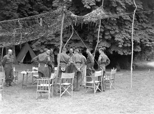 General Sir Bernard Montgomery (eighth from left) talking with Lieutenant-General Guy Simonds (ninth from left) and other senior officers of the 2nd Canadian Corps at Corps Headquarters in the Normandy bridgehead, France, 20 July 1944.