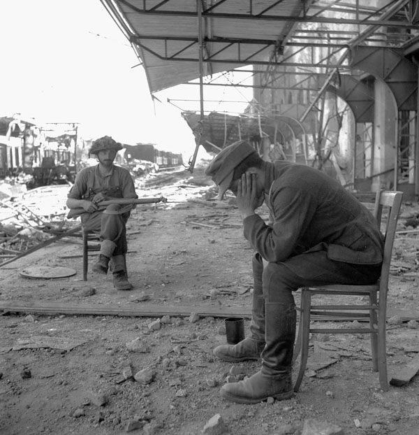 An unidentified Canadian soldier guarding a captured German officer, Vaucelles, France, 18 July 1944.