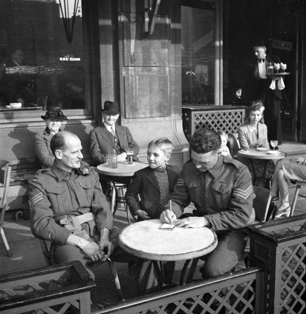 Sergeant G.S. Coen (right), Royal Canadian Army Service Corps (R.C.A.S.C.), signing autograph book for boy at café. Sergeant C.C.W. Campbell, Canadian Dental Corps (C.D.C.), is at left, Antwerp, Belgium, 17 September 1944.