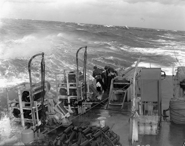 Naval personnel checking the stowage of depth charges on the quarterdeck of the frigate H.M.C.S. SWANSEA  in rough seas off Bermuda, January 1944.