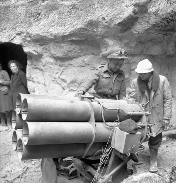 Private P.P. Beauchamp (left) of Le Régiment de Maisonneuve and Dr. Cohier examining a captured German Nebelwerfer 41 artillery rocket  launcher, Fleury-sur-Orne, France, 20 July 1944.