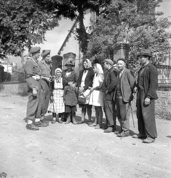 Corporals Dave Murrie (left) and Andy Jansen chatting with Polish refugees, St. Quentin, France, 16 August 1944.