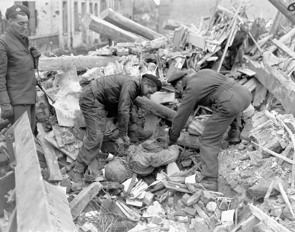 Sapper M.L. Rogers of the Mechanical Equipment Company, Royal Canadian Engineers (R.C.E.), and Private R.E. Osborn of The Cameron Highlanders of Ottawa (M.G.) clearing rubble off the body of a German soldier, Udem, Germany, 2 March 1945.