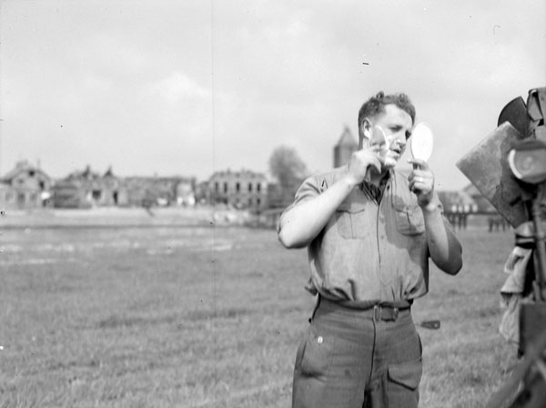 Lance-Bombardier R.W. Brull of the 3rd Anti-Tank Regiment, Royal Canadian Artillery (R.C.A.), shaving in a field outside Dalfsen, Netherlands, 13 April 1945.