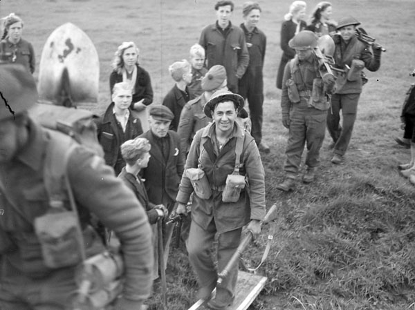 """Private A.J. Espanill of """"C"""" Company, Highland Light Infantry of Canada, boarding a barge, Dalfsen, Netherlands, 13 April 1945."""