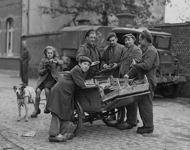 Corporal A. McLean and Sappers J.H.D. Pratte and P.E. Rivet, all of the Royal Canadian Engineers (R.C.E.), purchasing grapes from a Belgian with a dog-drawn cart, Bockhoute, Belgium, 20 October 1944.