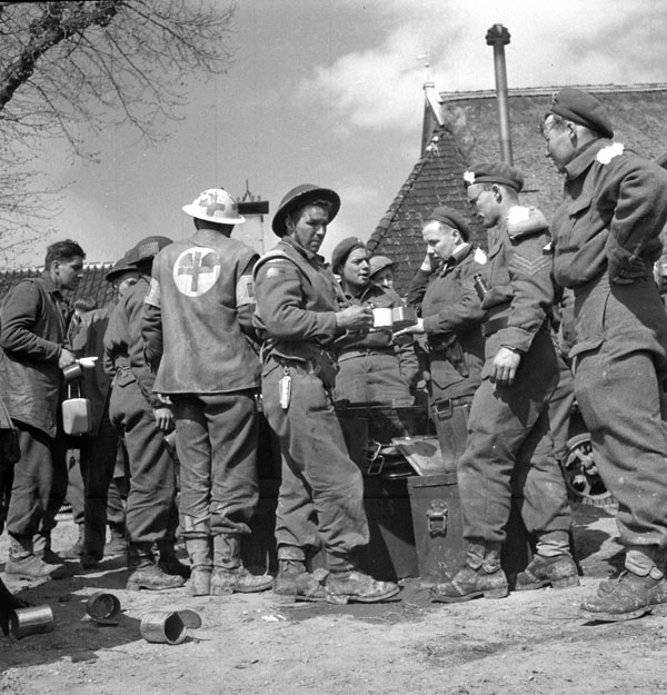 A platoon of The Royal Hamilton Light Infantry gathered at the regiment's Tactical Headquarters for their first hot meal in 24 hours, Groningen, Netherlands, 14 April 1945.